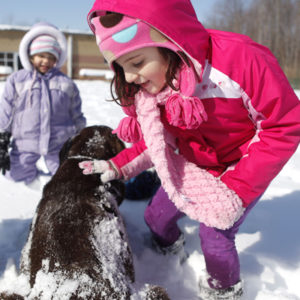 Children petting a dog out in the snow.