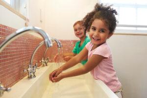 Two children wash their hands.